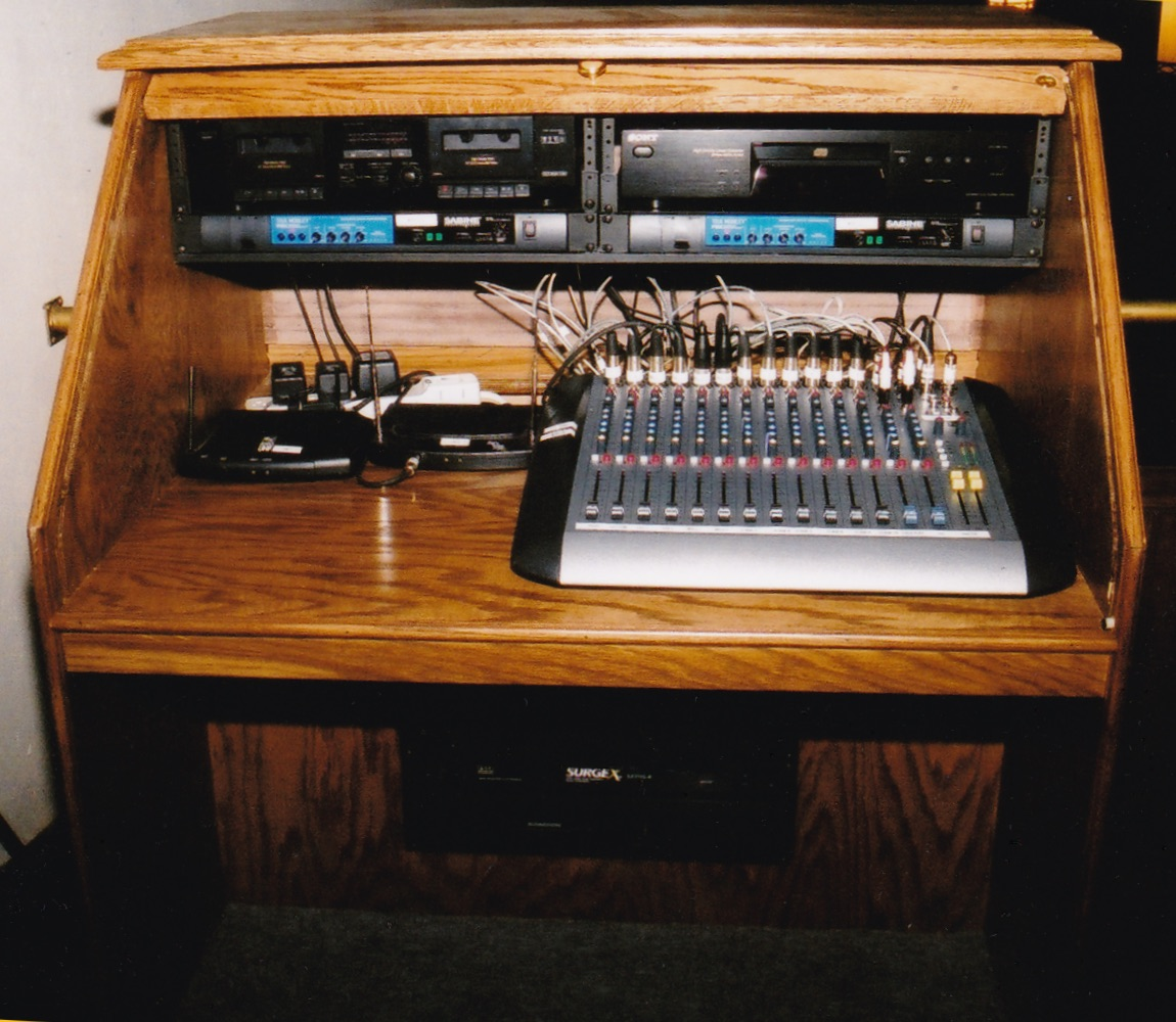 Figure 1: A simple table-top desk with wireless receivers on a ledge. Figure 2: A professionally-made console with power amps, etc. below the desk.